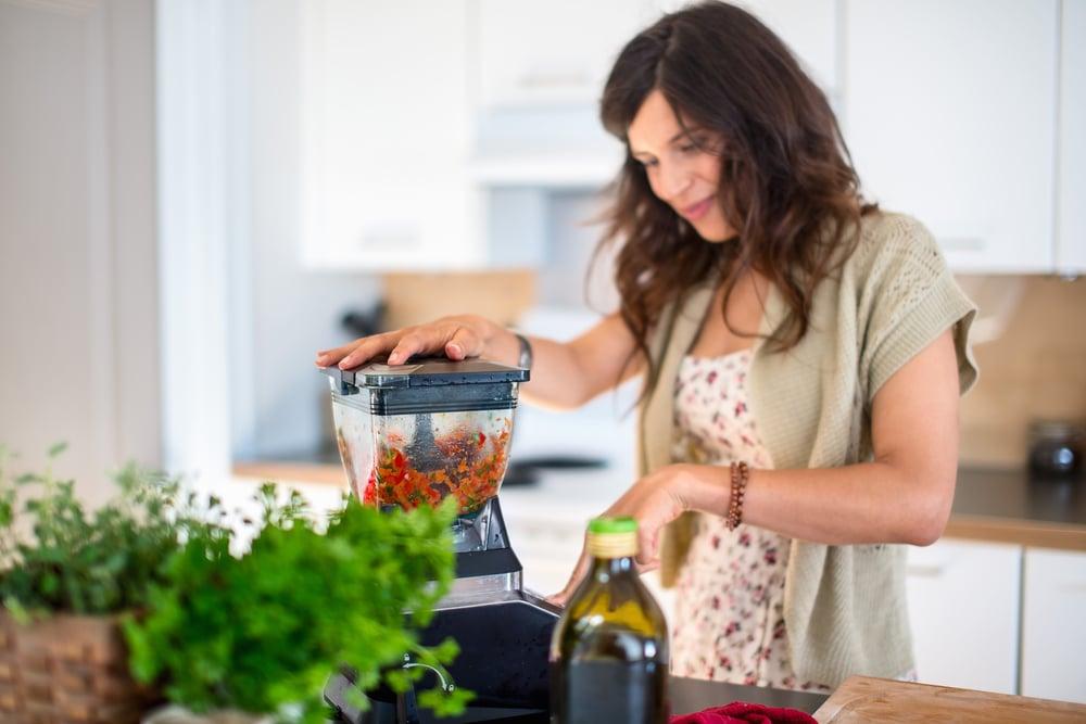 Health conscious woman using a blender