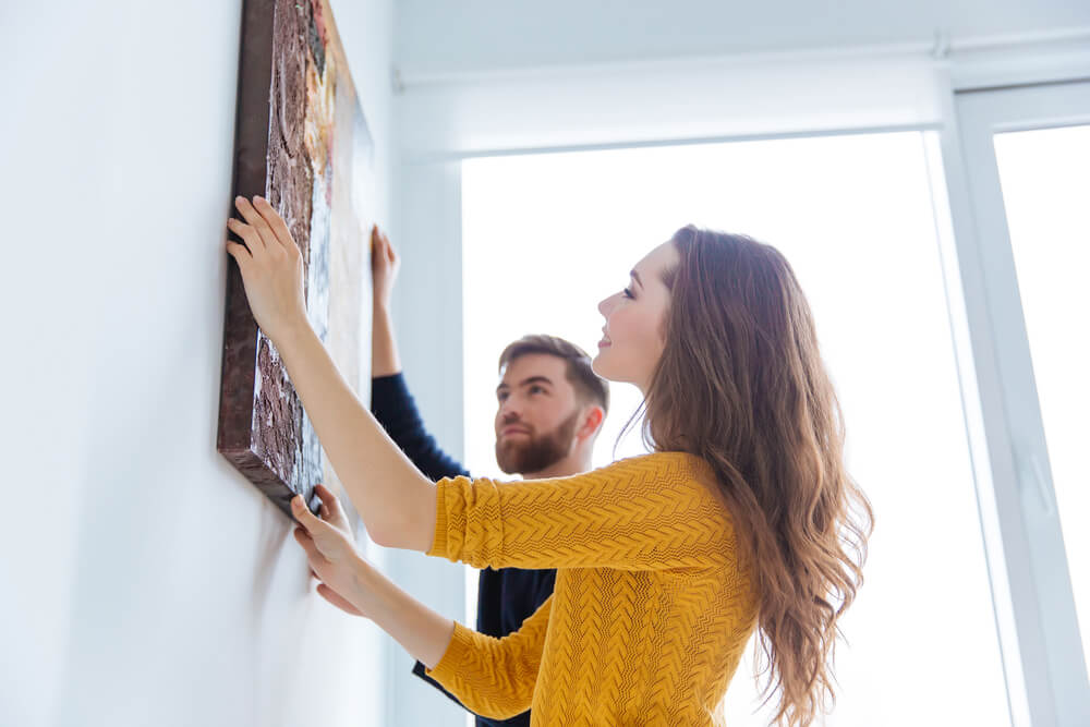 Happy couple hanging picture on the wall at home