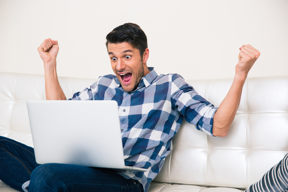 Portrait of excited man looking game on laptop at home