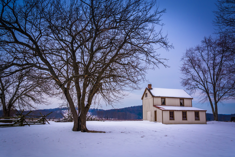 Small house and trees in a snow-covered field in Gettysburg, Pennsylvania.